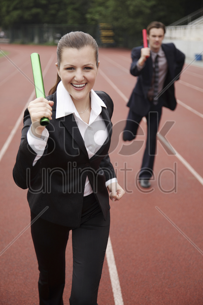 business people running in a relay stock photo
