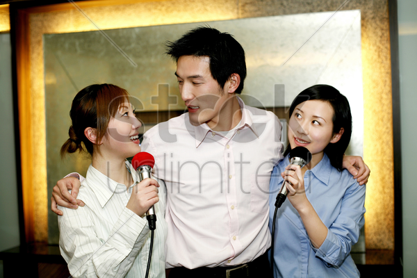 business people singing karaoke after work stock photo