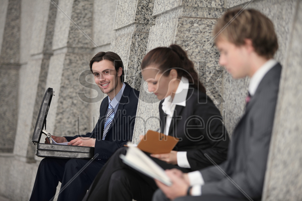 business people sitting at the side of a building stock photo