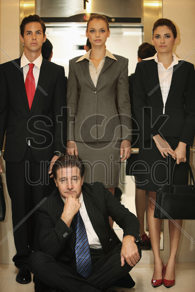 business people standing while businessman sitting on the floor of elevator stock photo