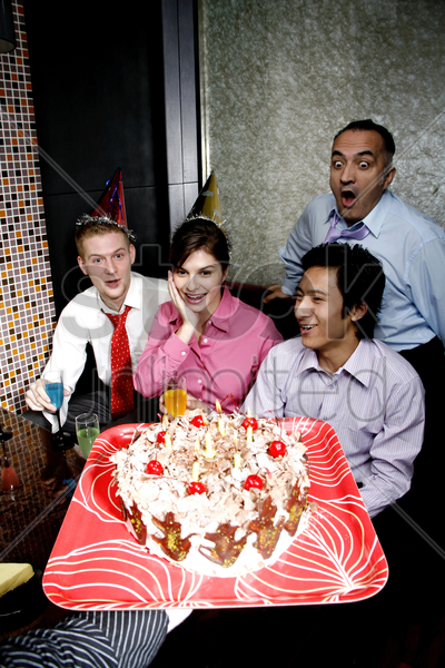 business people throwing a surprise birthday party for their female colleague stock photo