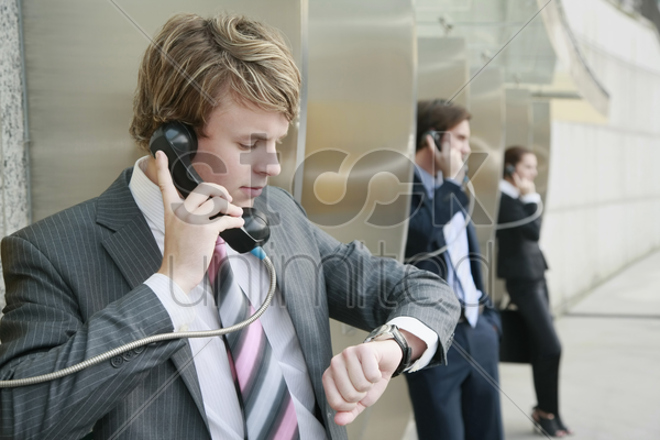 business people using public telephones stock photo