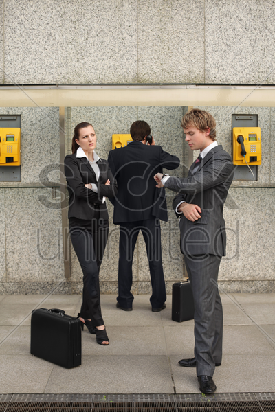 business people waiting for businessman talking on public telephone stock photo