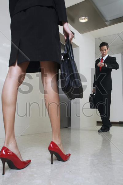 business people waiting for elevator, businessman checking the time on his watch stock photo