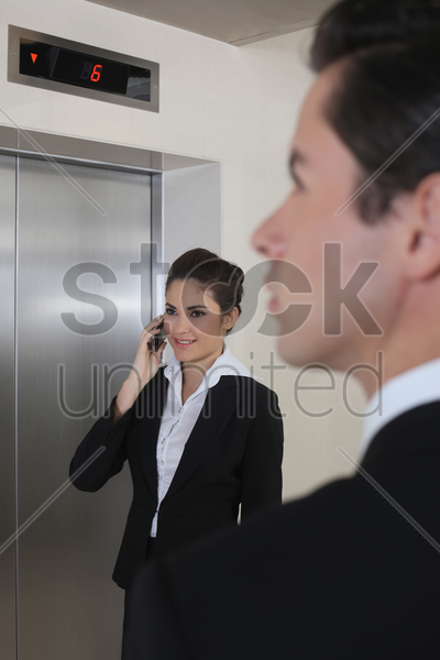 business people waiting for elevator, businesswoman talking on the phone stock photo