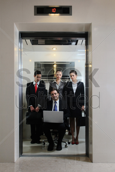 business people watching businessman sitting on office chair and using laptop in an elevator stock photo