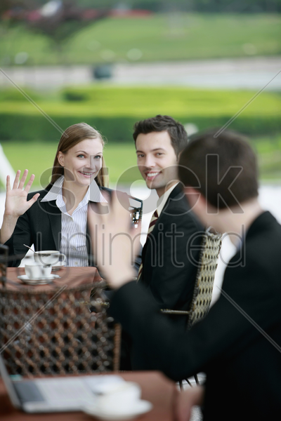 business people waving at each other at outdoor cafe stock photo