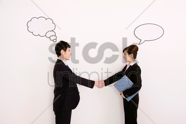 business people with thought and speech bubble above their heads, shaking hands stock photo