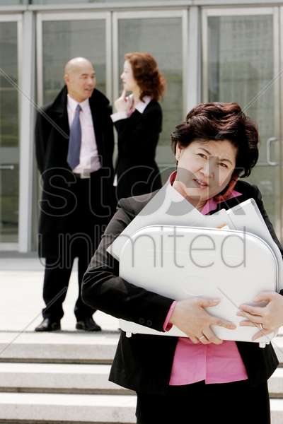 business woman talking on the hand phone while carrying a briefcase of documents stock photo