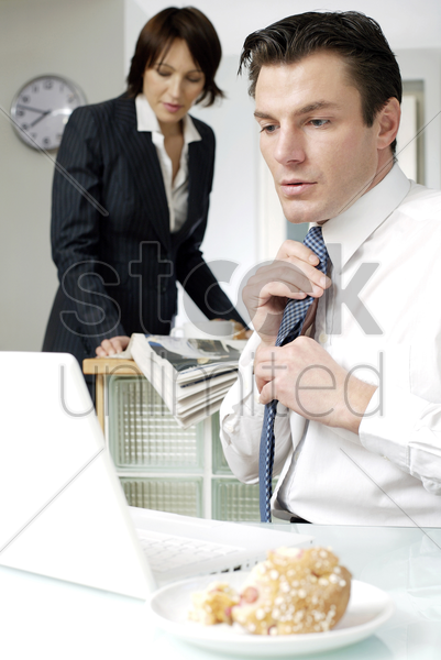businessman adjusting his tie while looking at laptop stock photo