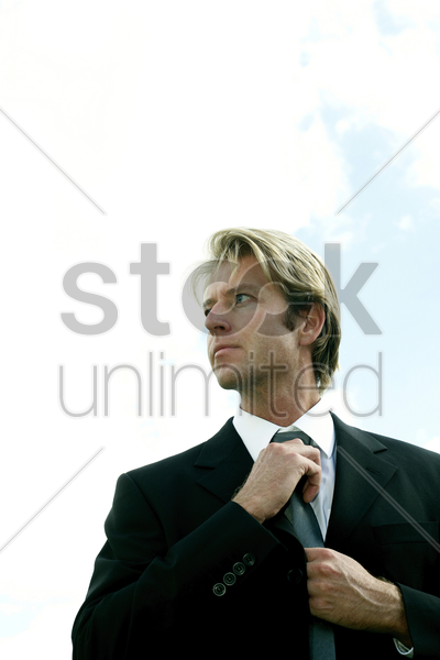 businessman adjusting his tie while looking away stock photo