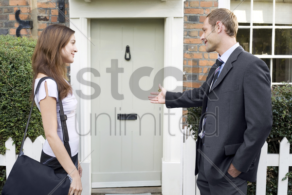 businessman allowing businesswoman to walk before him stock photo