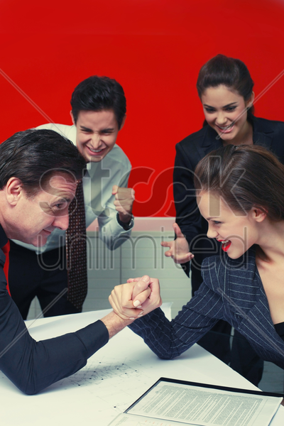 businessman and businesswoman arm wrestling on table, the others cheering stock photo