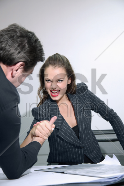 businessman and businesswoman arm wrestling on table stock photo
