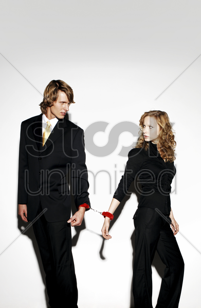 businessman and businesswoman being cuffed together stock photo