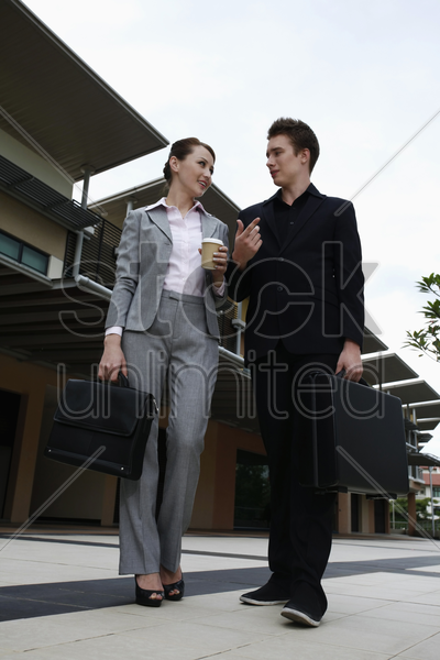 businessman and businesswoman chatting while walking together stock photo