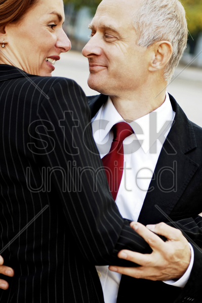 businessman and businesswoman dancing together stock photo
