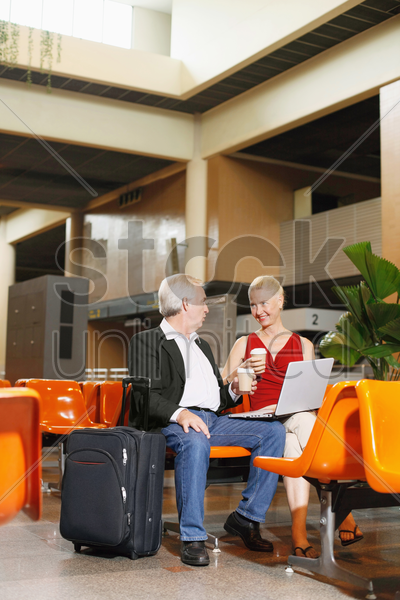 businessman and businesswoman enjoying coffee in airport lounge stock photo