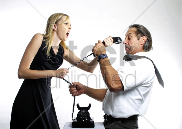businessman and businesswoman fighting over a phone stock photo