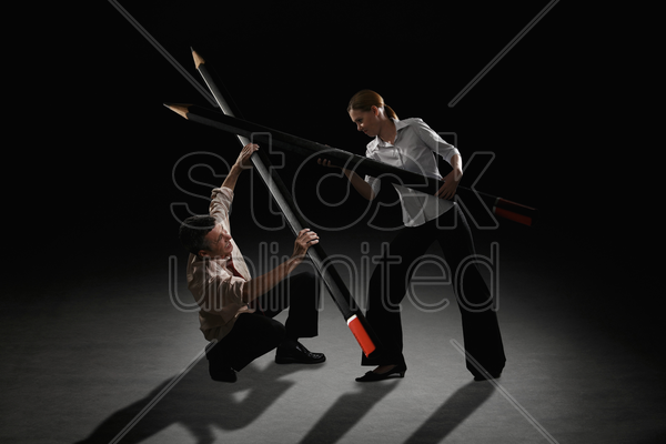 businessman and businesswoman fighting using giant pencils stock photo