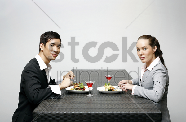 businessman and businesswoman having dinner together stock photo