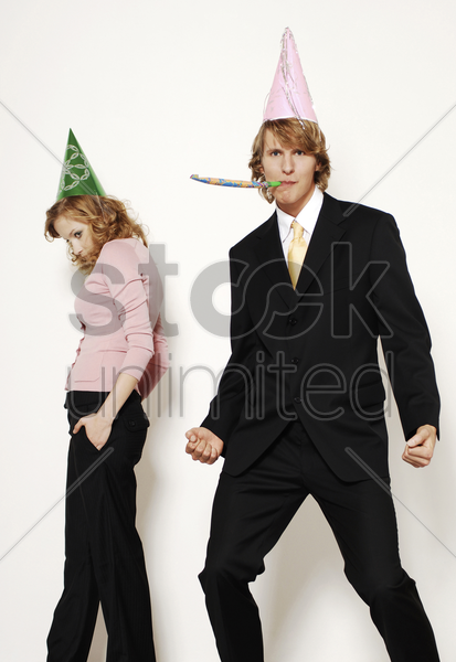 businessman and businesswoman in party hat stock photo