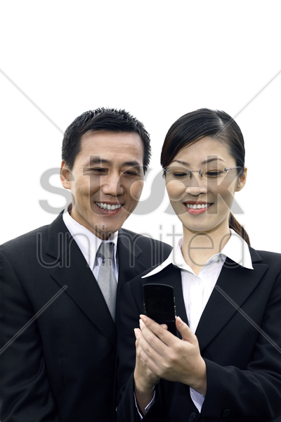 businessman and businesswoman looking at mobile phone stock photo