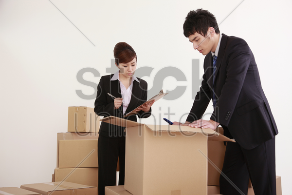 businessman and businesswoman looking inside opened cardboard box stock photo