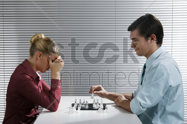 businessman and businesswoman playing chess game stock photo