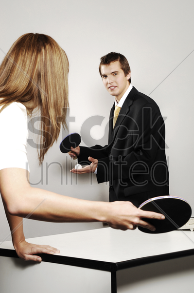 businessman and businesswoman playing table tennis in the office stock photo