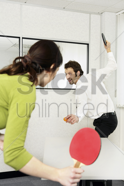 businessman and businesswoman playing table tennis stock photo