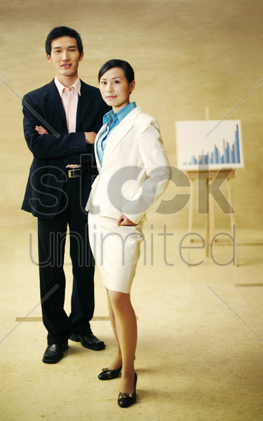 businessman and businesswoman posing near a chart stock photo