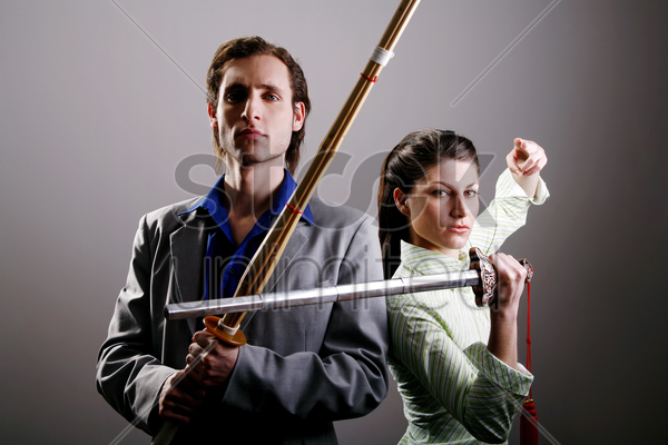 businessman and businesswoman practicing different martial art stock photo