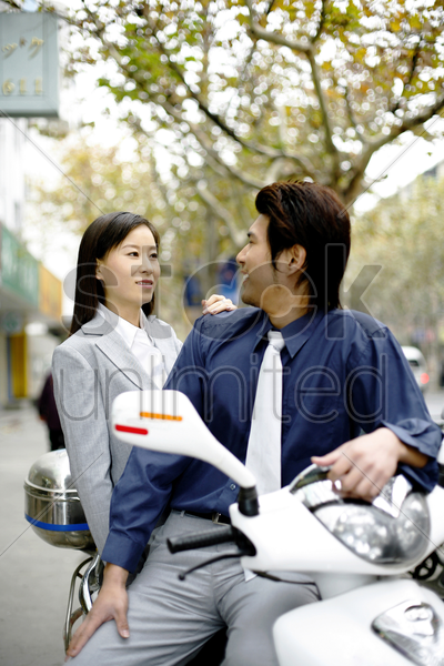businessman and businesswoman sitting on the scooter talking stock photo