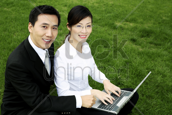 businessman and businesswoman smiling at the camera while sharing a laptop stock photo