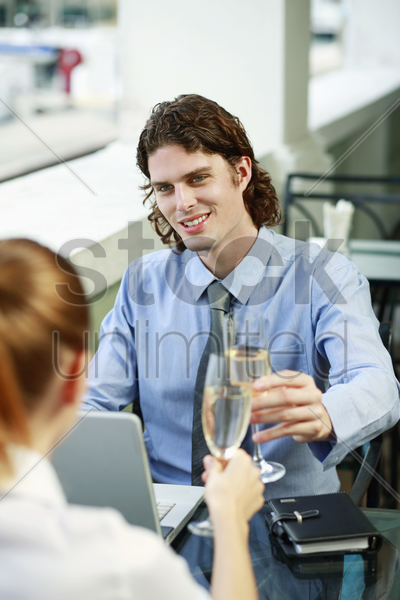 businessman and businesswoman toasting champagne stock photo