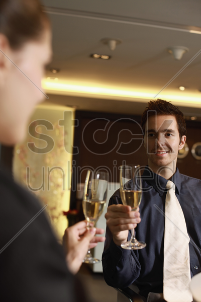 businessman and businesswoman toasting drinks stock photo