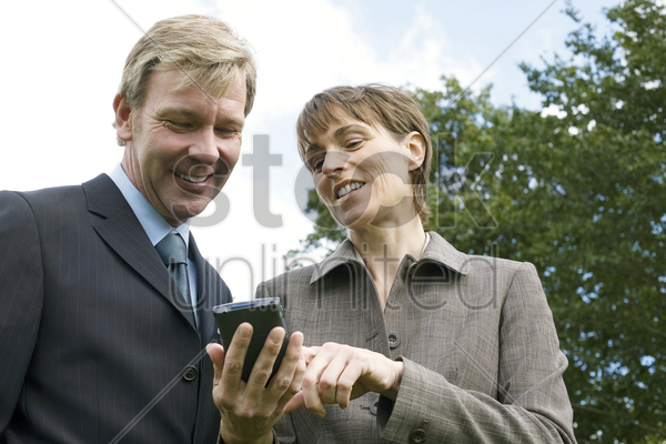 businessman and businesswoman using pda stock photo