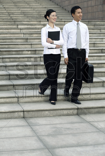 businessman and businesswoman walking together stock photo