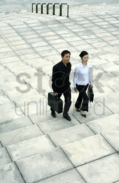 businessman and businesswoman walking up the stairs stock photo