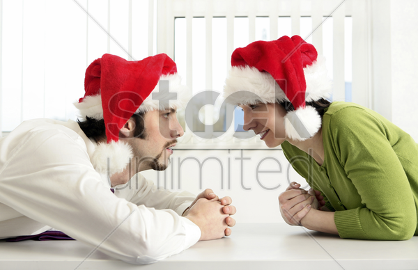 businessman and businesswoman wearing christmas hat stock photo