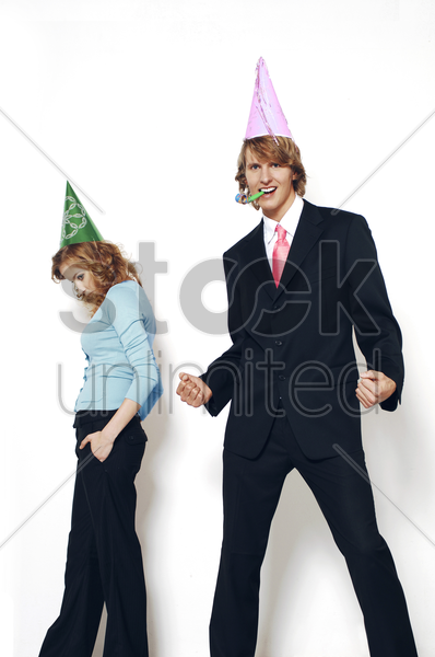 businessman and businesswoman wearing party hats stock photo