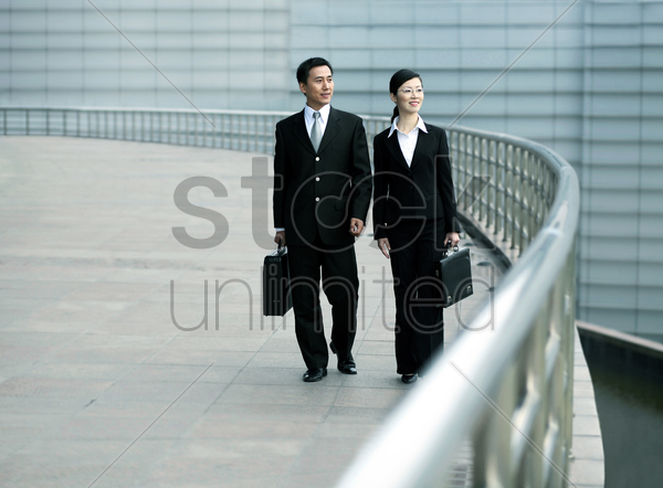 businessman and businesswoman with briefcase walking together stock photo