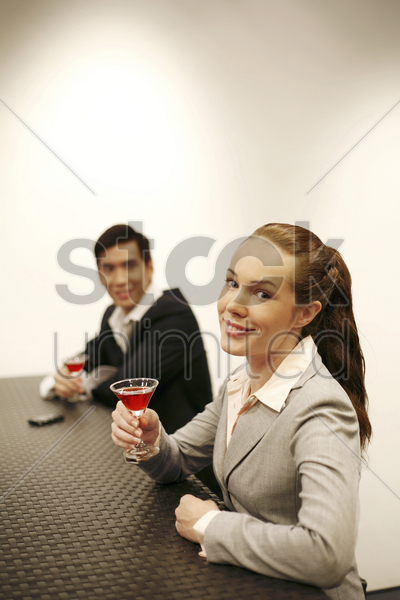 businessman and businesswoman with glasses of red wine stock photo