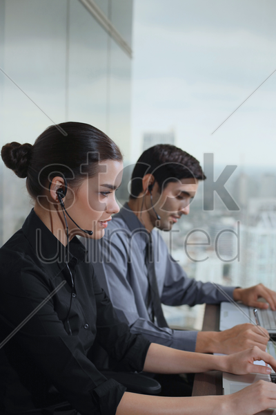 businessman and businesswoman with telephone headsets stock photo