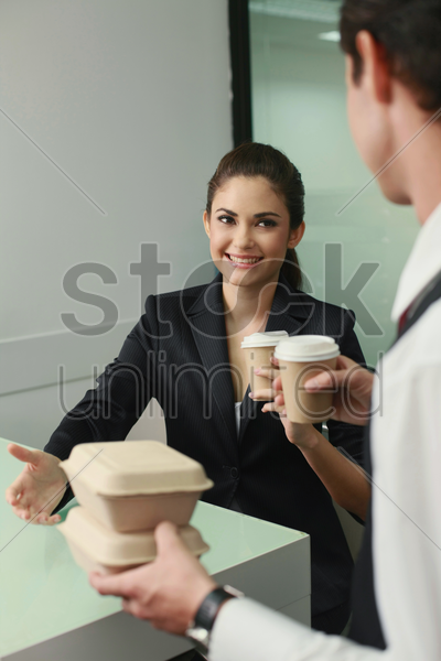 businessman and businesswoman with their take-out food stock photo