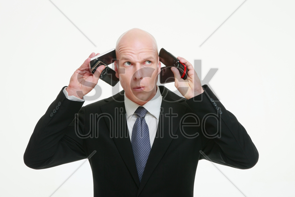 businessman answering a few phone calls at the same time stock photo
