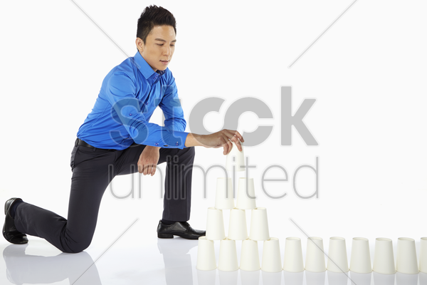 businessman arranging disposable cups stock photo