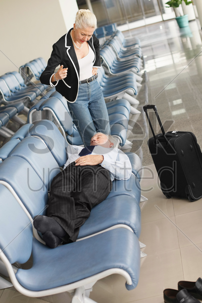 businessman asleep on seat in airport lounge, businesswoman standing over him pointing finger stock photo