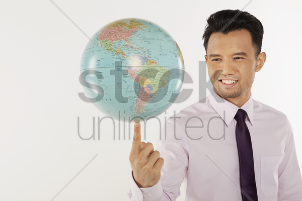 businessman balancing a globe at the tip of his finger stock photo